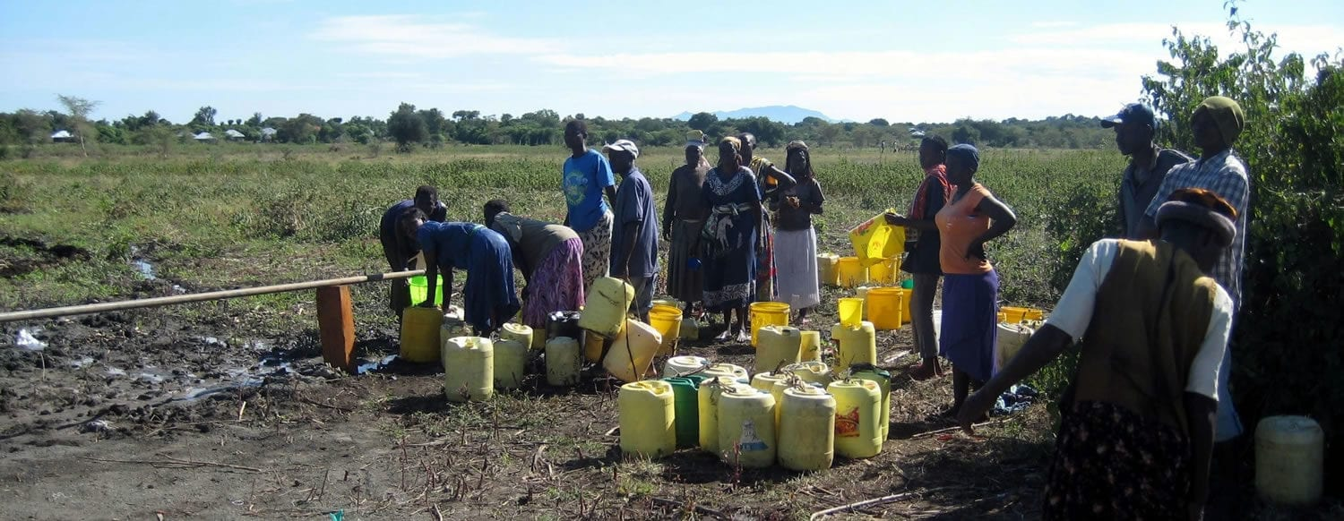Villagers collecting water with jerrycans from a RaHa system tap